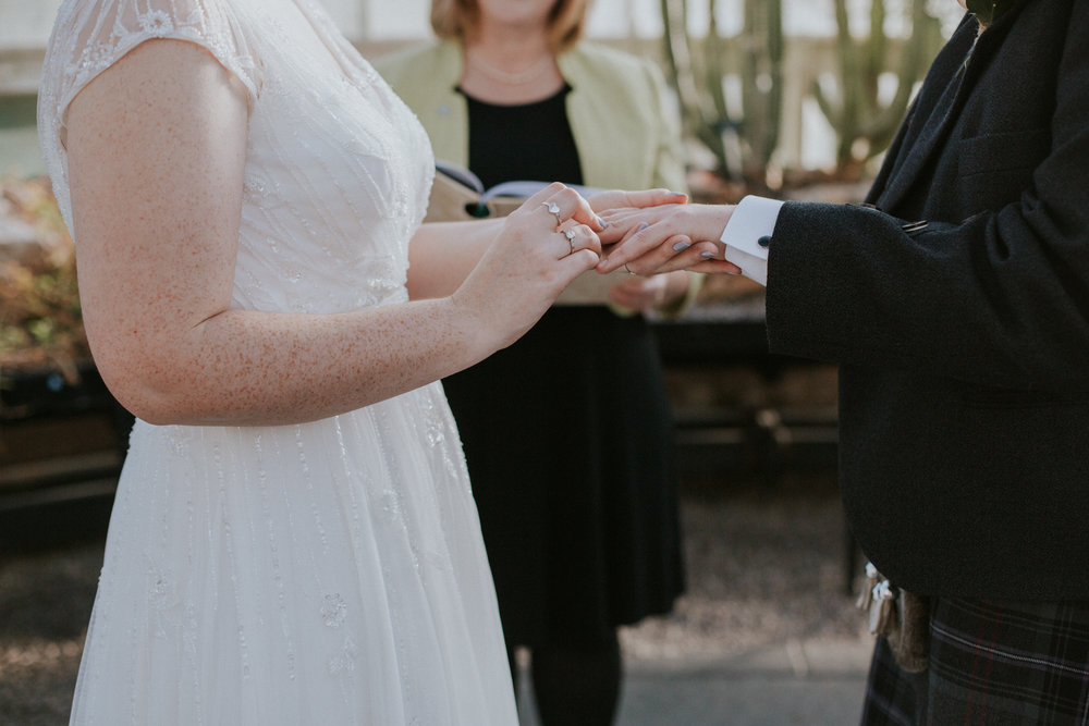 The bride is putting the wedding ring on groom's fingers