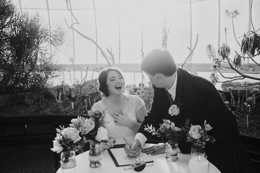 Signing the marriage certificate and the bride is happily laughing