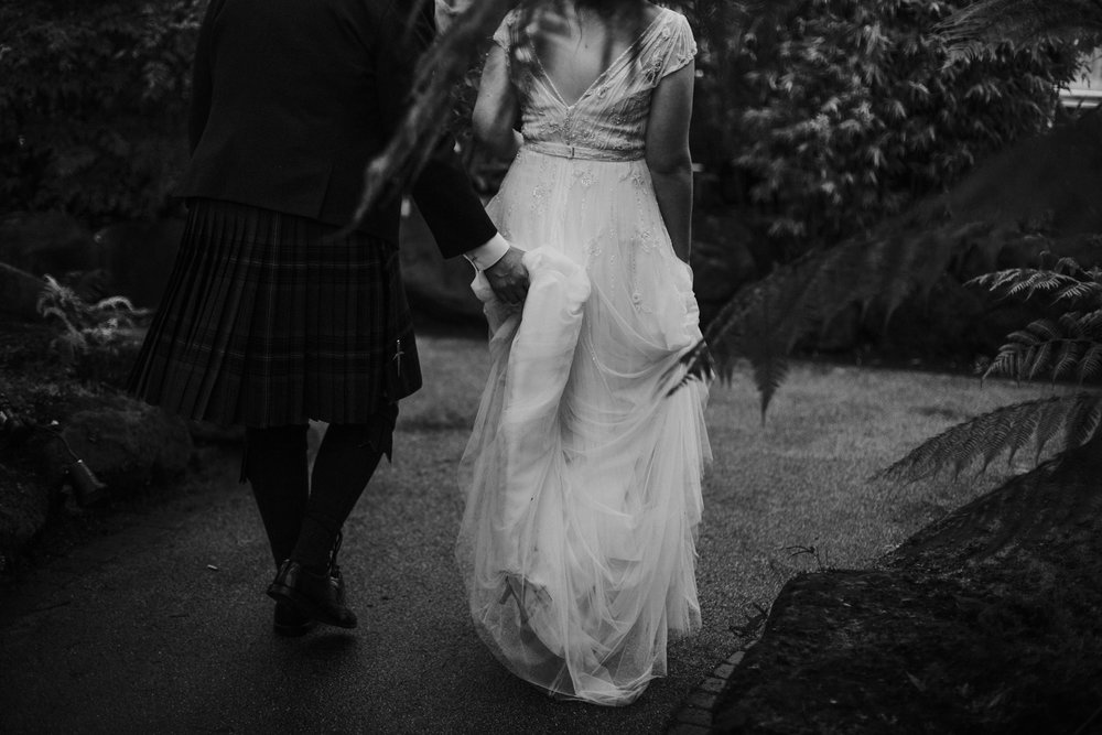 Groom holds the bride's dress while they walk at the Botanic Gardens in Glasgow