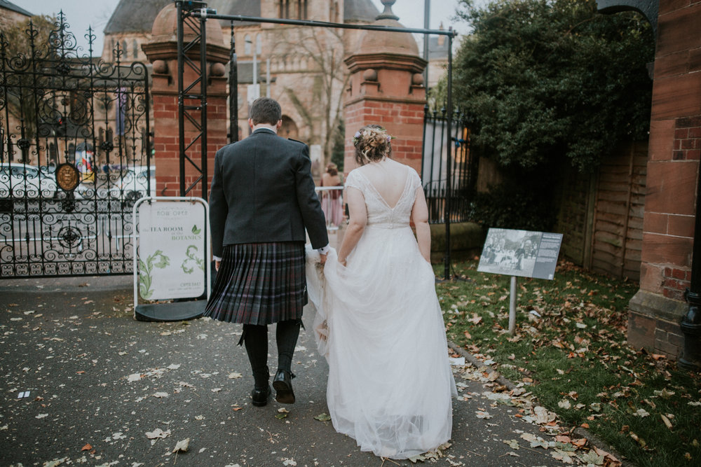 Groom and bride are walking out from the Botanic Gardens