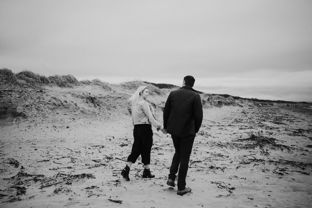 The engaged couple is walking together on the Ayrshire beach in Troon