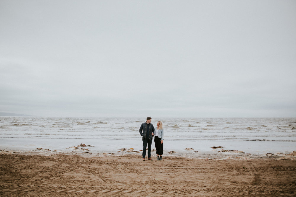 The couple is standing and looking to each other on the edge of the sea in Troon beach