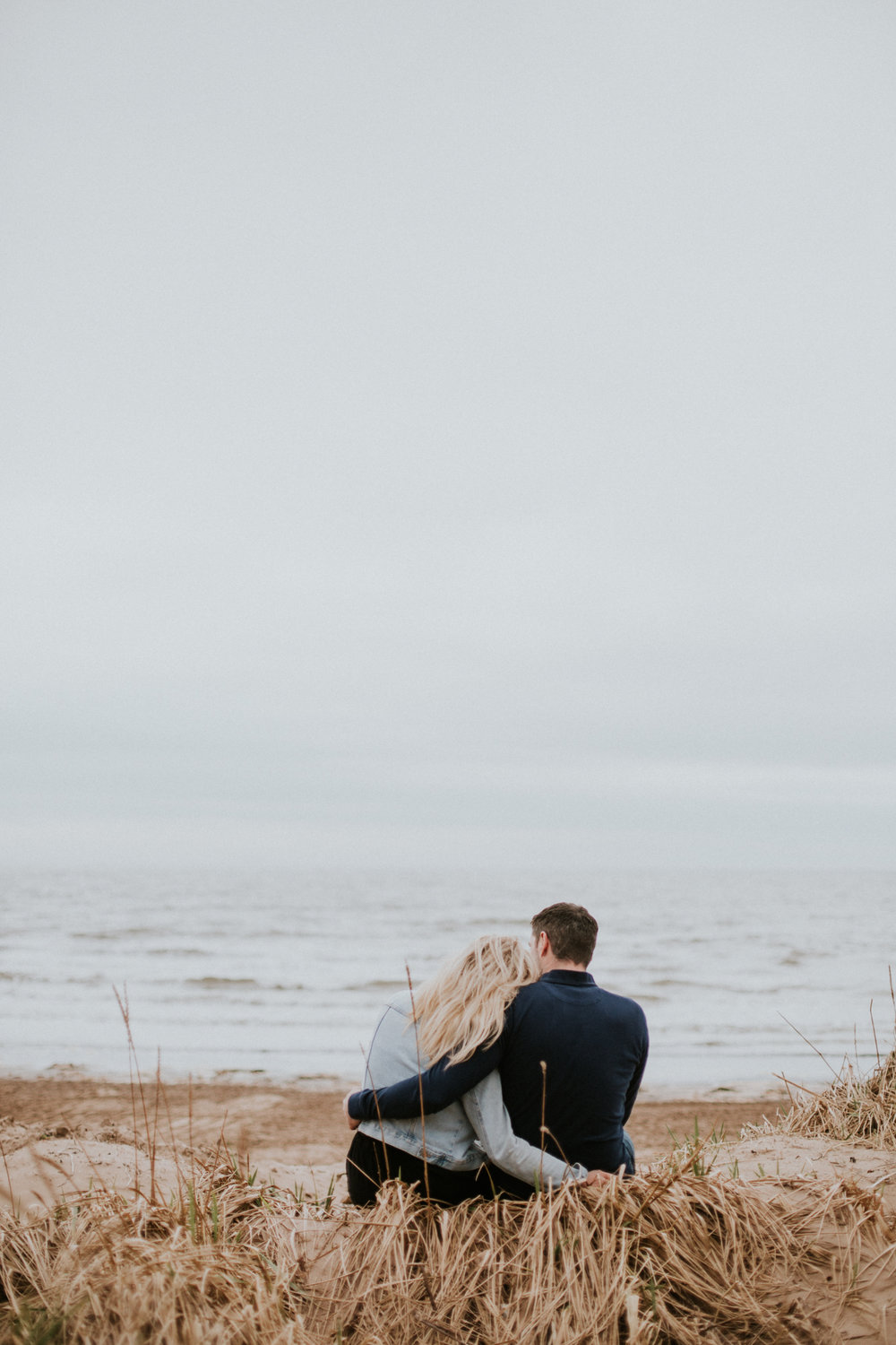 The couple is sitting and cuddling each other and looking at the sea in Troon, Ayrshire