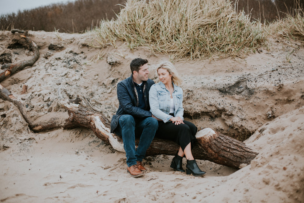 Happy couple sitting together on the beach in Troon
