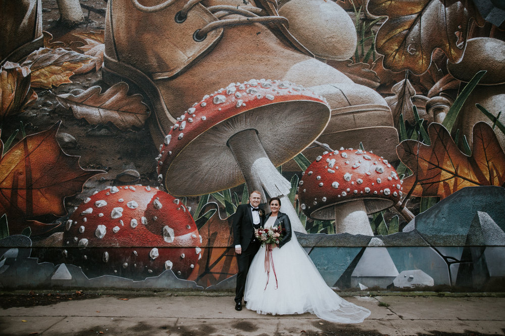 Couple is standing next to the mural wall in Glasgow for their couple shoot