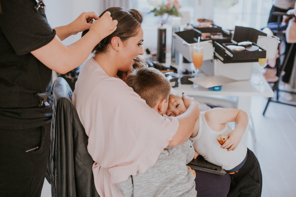 Bride cuddles with her sons and nephew