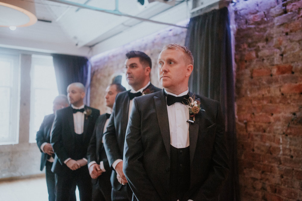The groom with his groomsmen is awaiting for the bride to come in the aisle of 29 private member club in Glasgow