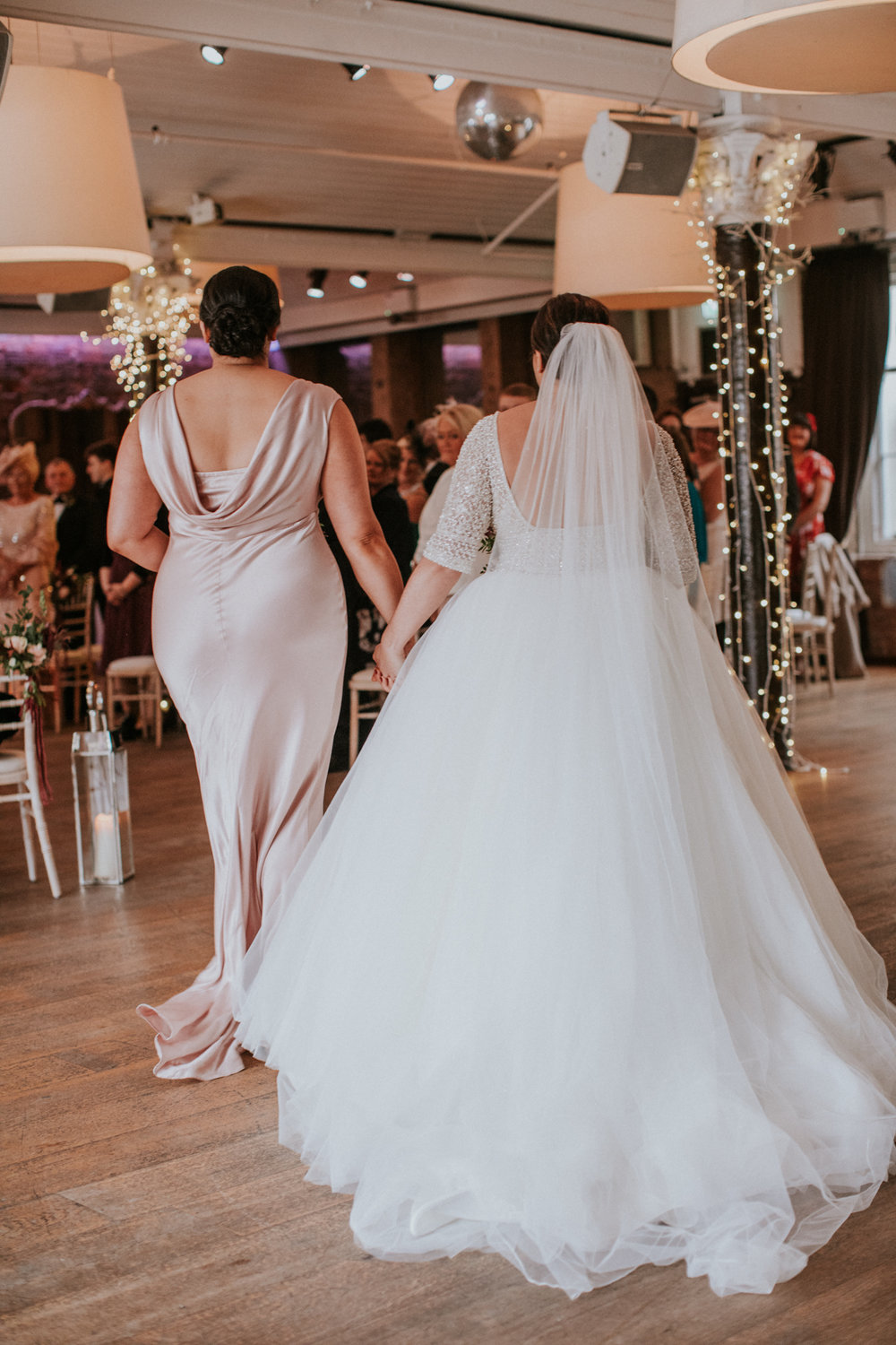 The bride is walking down the aisle with her sister