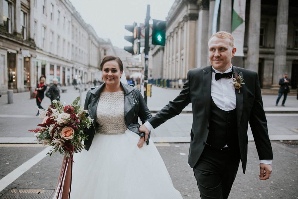 The couple is walking on the street of Glasgow city