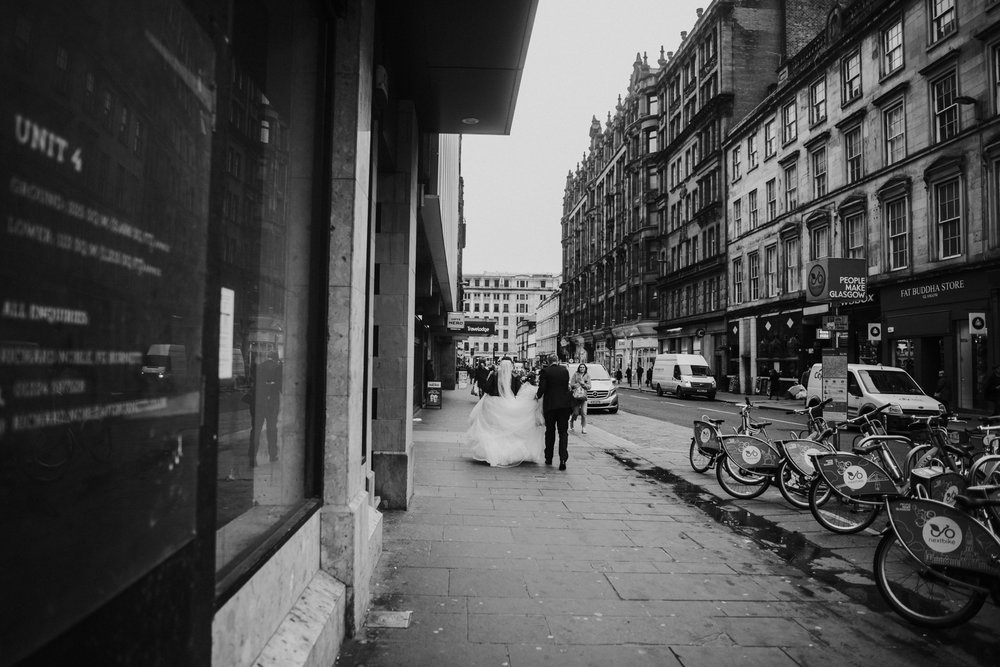 The newlywed couple walk together on the street of Glasgow, Scotland