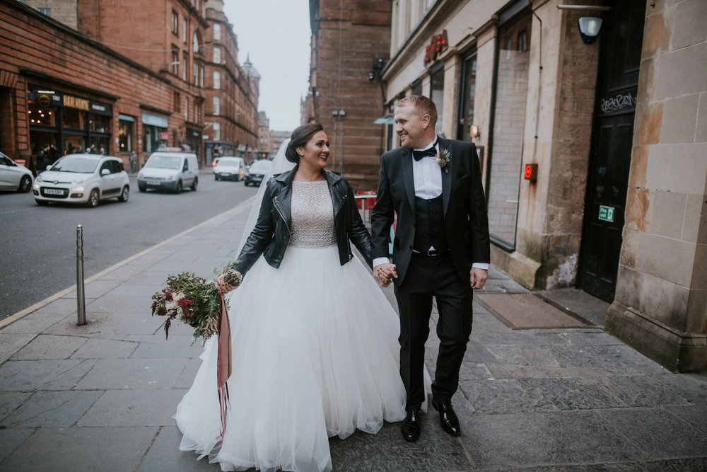 The bride and the groom are walking together with the happy smiles on their faces