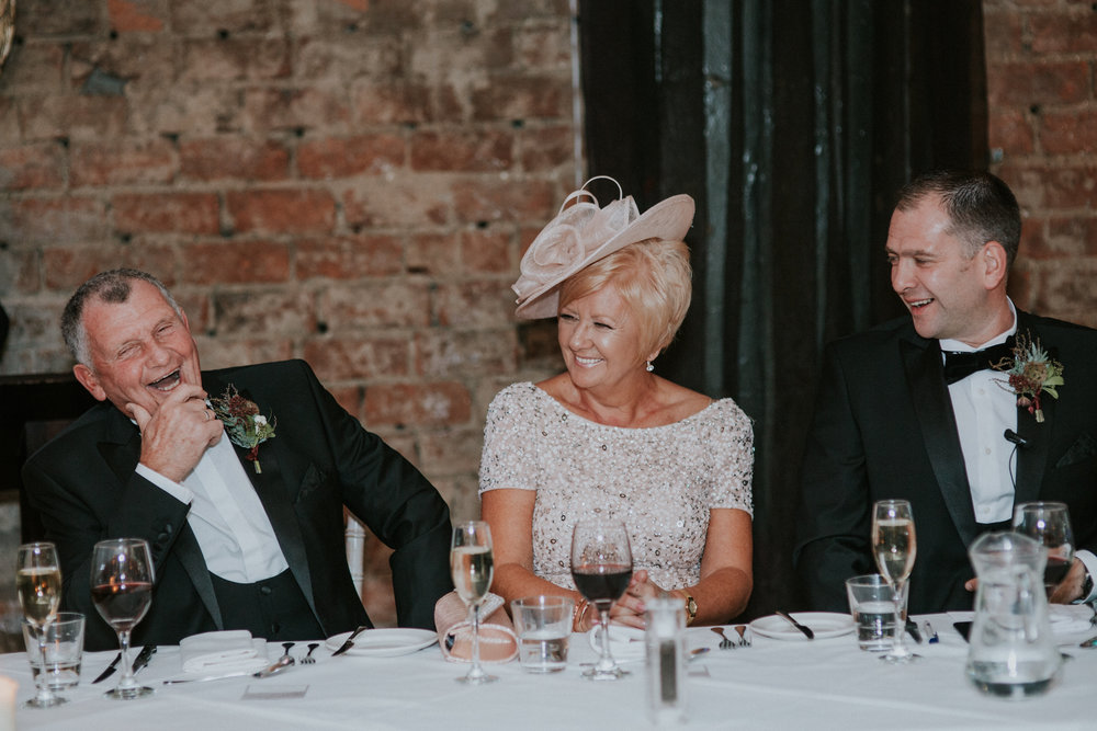Capture the moment of the groom's parents enjoying their time at the speeches
