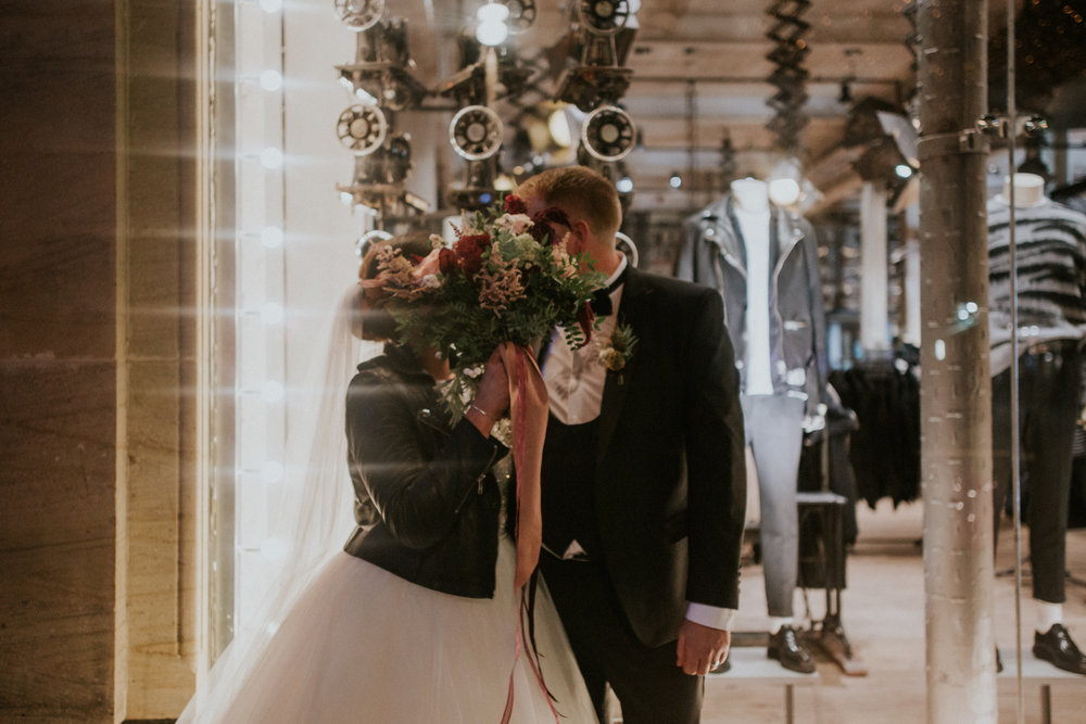 The couple is hiding the kiss by the wedding flower bouquet of the Floral Menagerie