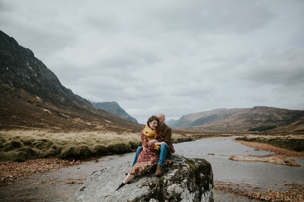 The engaged couple is sitting on the rock in the Scottish Highlands