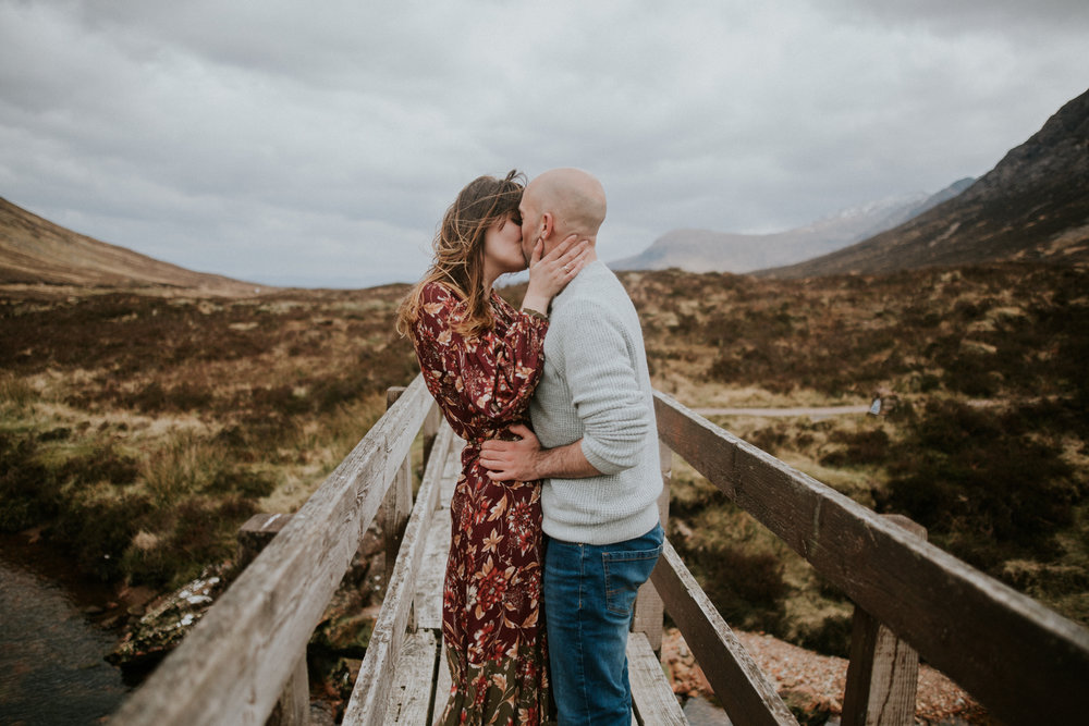 The couple is kissing each other in the stunning Scottish Highlands, Glencoe Scotland