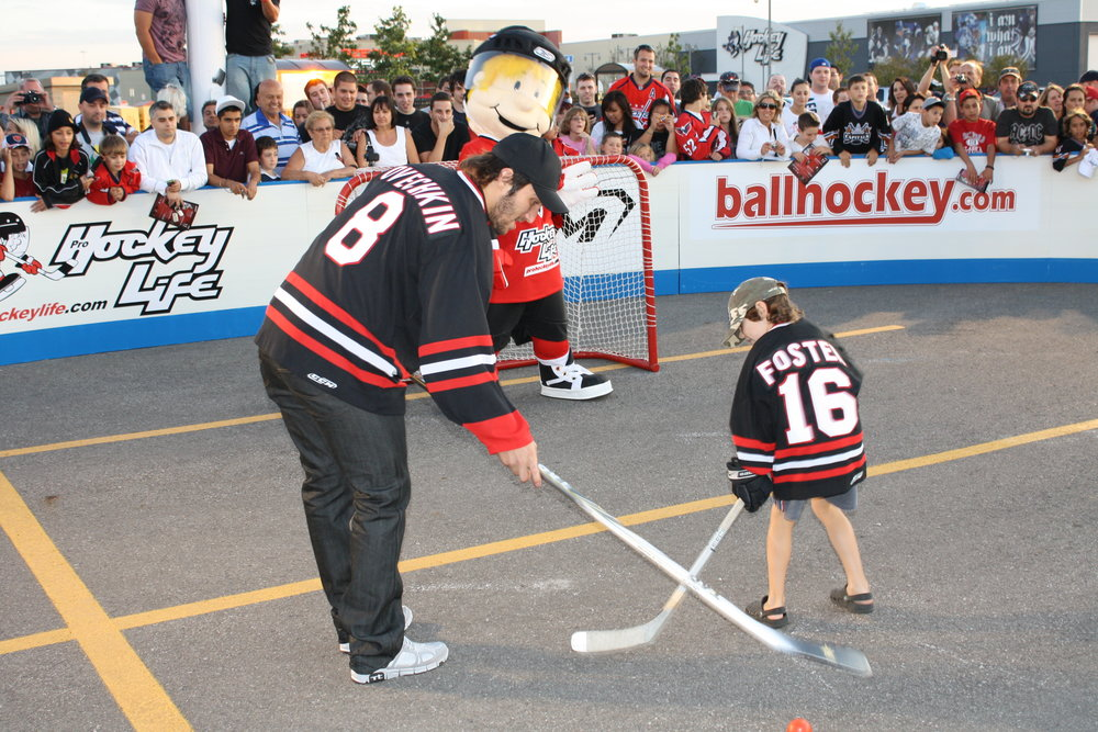 Alex Ovechkin plays ball hockey with a child at a pop up event run with Pro Hockey Life & CCM