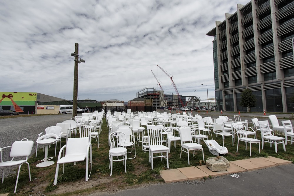 185 empty white chairs of all shapes and sizes.
