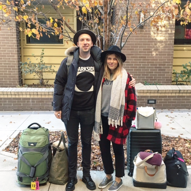 tim + me in our matching travel wear, posing with our entire life, packed up in bags.