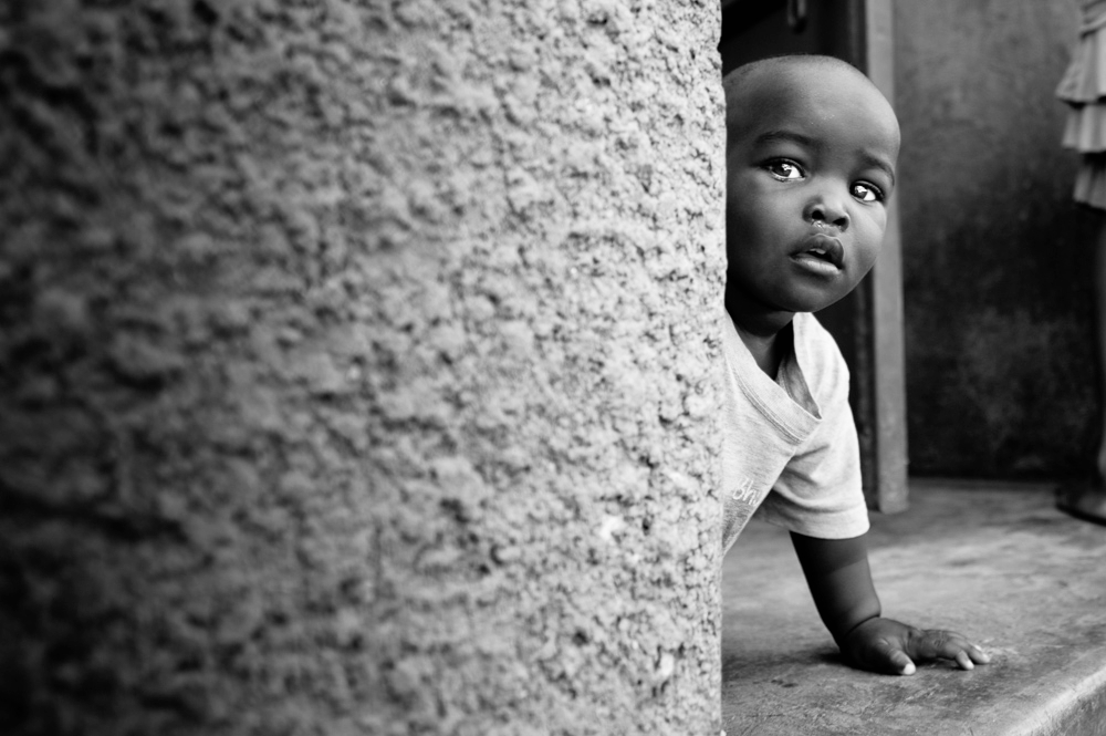 A young boy peeks across the wall with curiosity.