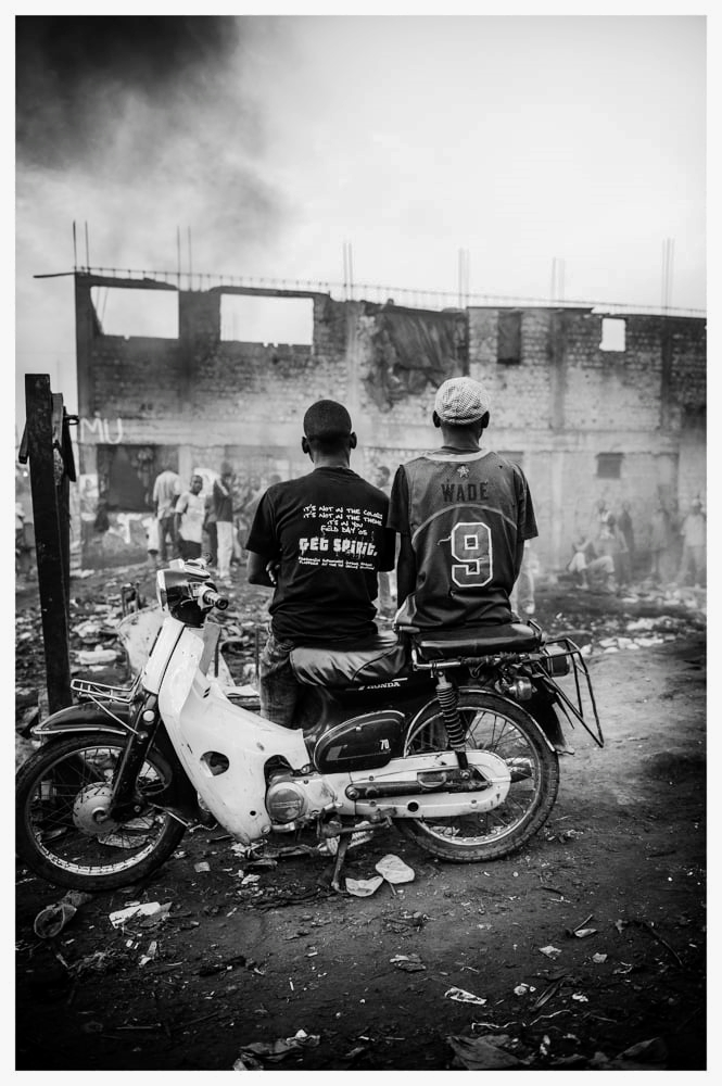 Two Teenage Boys From Kampala's Slum Sit And Watch As A Builders Billows With Smoke.