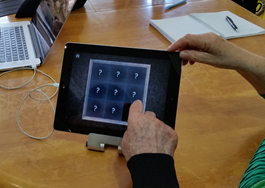 A resident interacting with the app revealing a picture vis turning tiles.