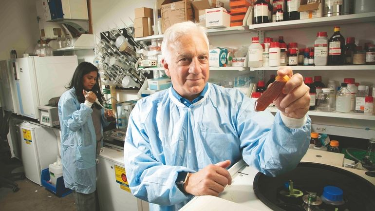 Image of Ray Sambrotto holding a vile in a laboratory setting.