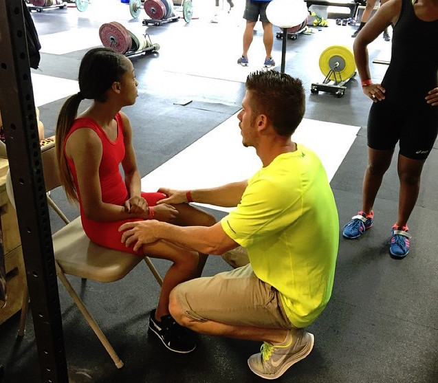 Tyler helping prepare one of his athletes who is about to compete in a WEIGHTLIFTING meet