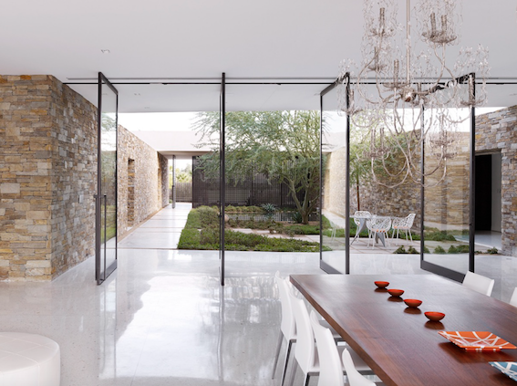 The vertical scale of the glass doors are complemented by the high courtyard walls and the height of the tree within the Courtyard.