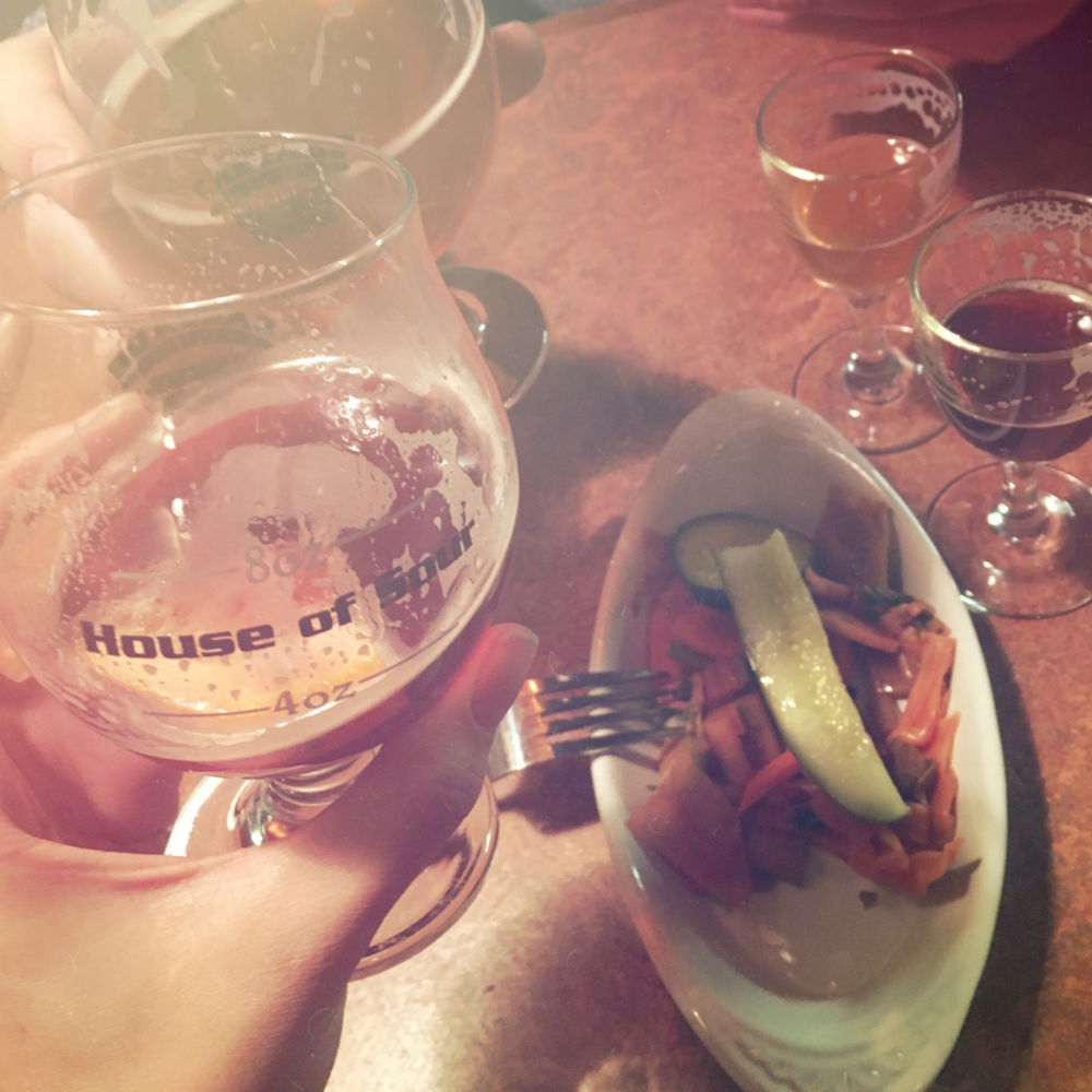 Glueh Kriek with a slice of orange and plate of pickled veggies on the side.