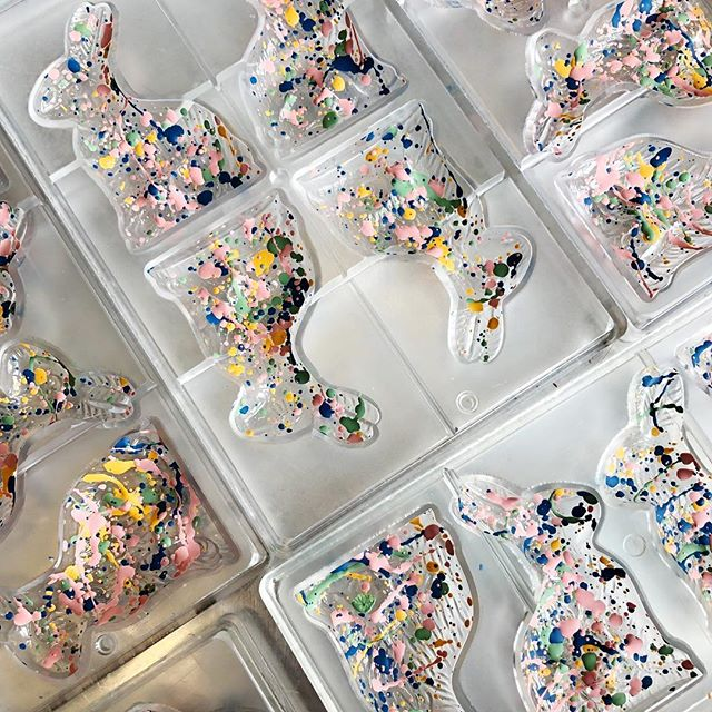Here's a look at how we make our Caramel Bunnies! First we start by splattering bunny molds with colored cocoa butter, we then coat the molds with dark chocolate, add in the most amazing tree leches caramel you'll ever have in your life, and then add more chocolate to the back!!🤩🍫