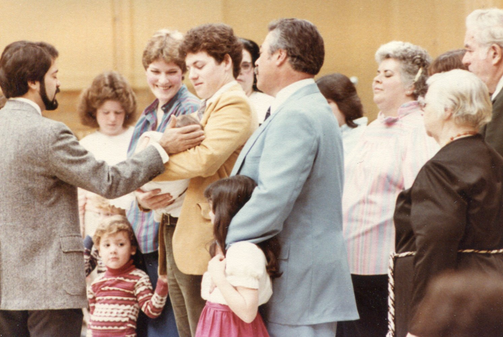 Special prayers of dedication for Paul Spitzer's new grandson, Kyle Spitzer. Paul W. Spitzer stands with his arm around daughter Joy's shoulder; surrounded by his family. Sunday before Thanksgiving, 1983.