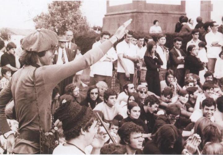 Un asistente levanta el brazo haciendo el saludo fascista. Al fondo, un hombre con gafas oscuras luce una gorra con una esvástica
