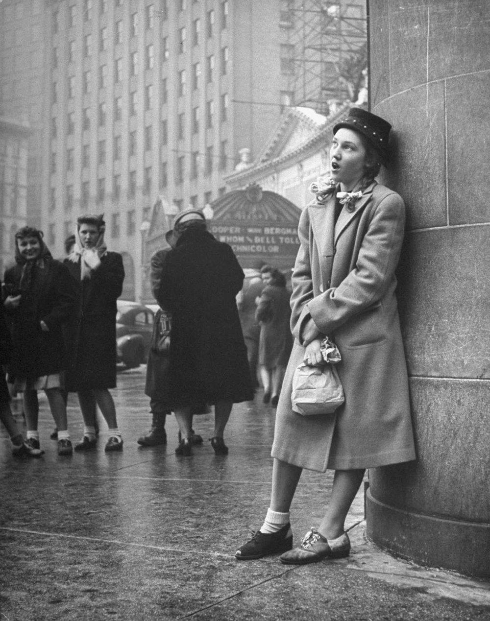 Una chica, pretendiente a entrar en un club de chicas, canta en una esquina durante una prueba de iniciación.  LIFE
