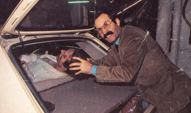 Eleuterio haciendo esfuerzos para lograr meter en su coche a su odioso  alter ego