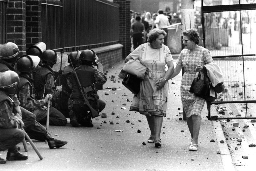 Dos mujeres pasean en medio de los disturbios por la visita en 1977 de la reina de Inglaterra al norte de Irlanda. Fotografía: Michael Ward