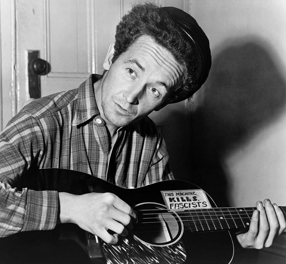 Woody Guthrie en 1943 con una de las dos guitarras en las que colocó su famosa frase. Fotografía: Al Aumuller/ New York World-Telegram and the Sun