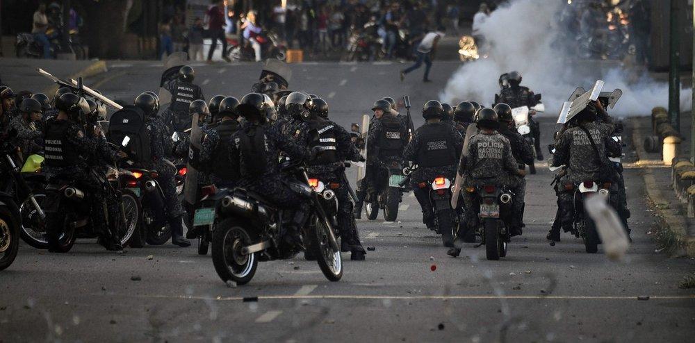 Policías en moto disparan a los manifestantes. Fotografía: AFP