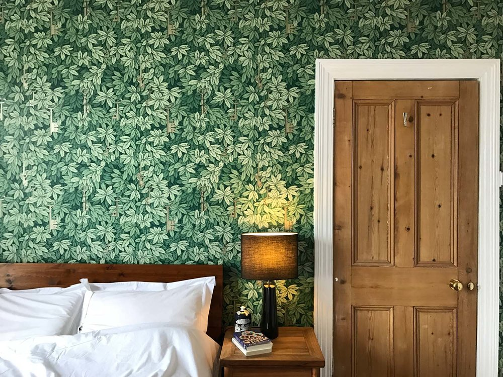 Fornasetti gold keys wallpaper in a bedroom