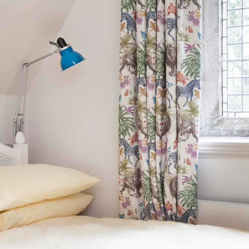 Dussk animal print curtains and blue Angelpoise lamps in the bedroom/Photo: Susie Lowe