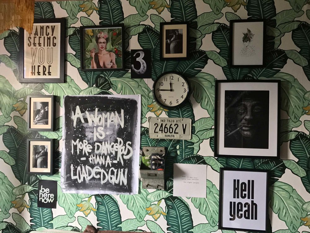 A gallery wall in Nicola's bathroom with its The Loft And Us banana leaf wallpaper that her husband didn't choose