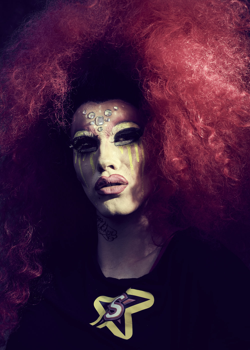 Ambiguous as to how this Drag Queen arrived in front of the camera. The S t-shirt stands for superstar?