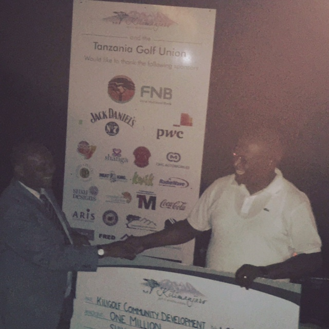 Kiligolf's Mr Kessy accepting a Tsh 1,000,000 cheque from Tanzania's Sports Minister Nape Nnauye for the Kiligolf Community Development Programme.