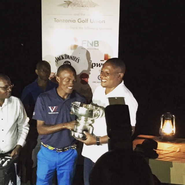 Robinson Owiti receiving the Tanzania Open trophy from Minister Nape Nnauye
