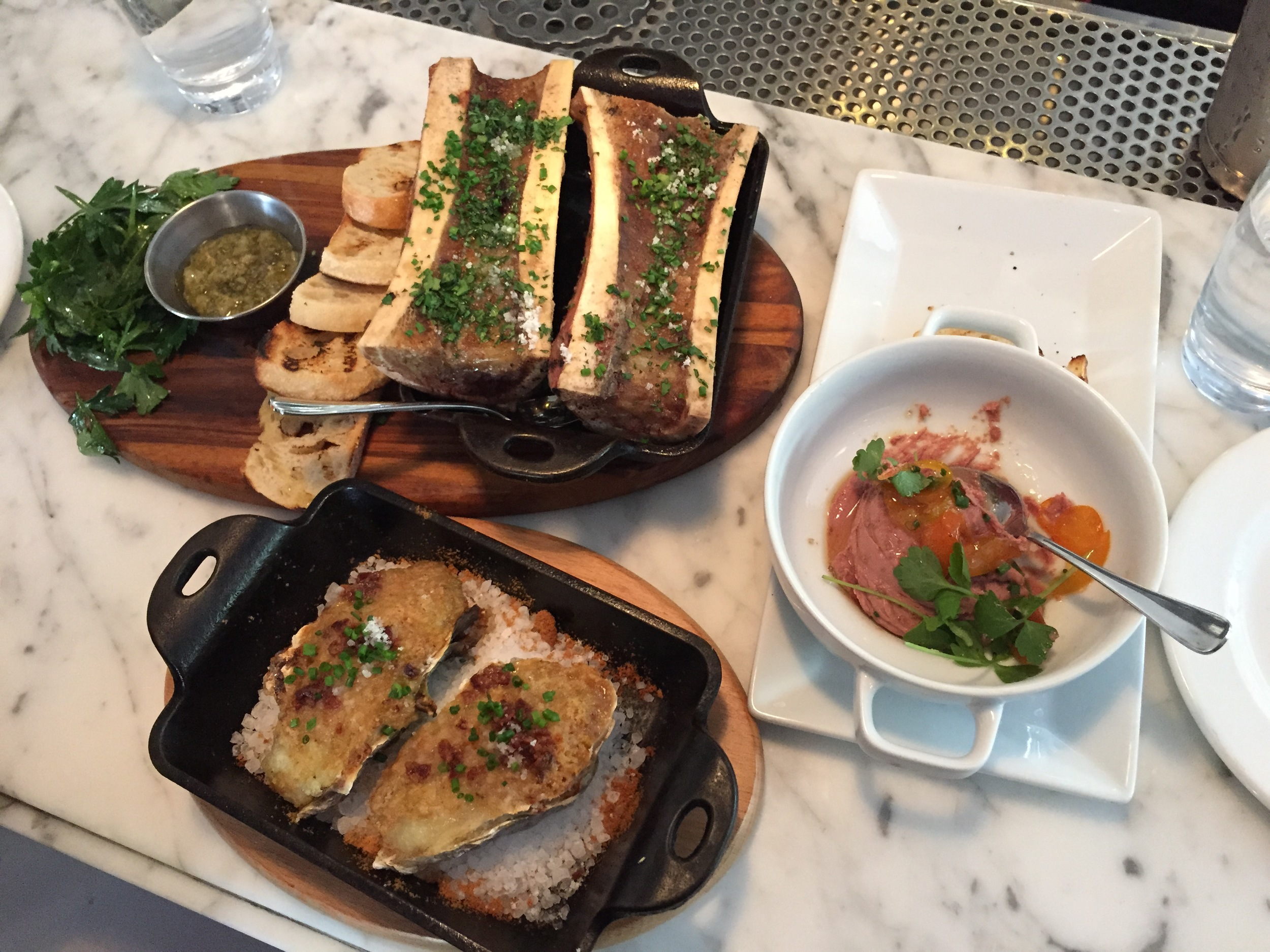 Clockwise from upper left: roasted bone marrow, duck liver mousse, baked oysters.