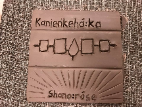 Kanien'keha:ka means People of the Flint (also known as Mohawk People) The middle design is the Iroquois Confederacy symbol, Haudenosaunee, also known as 6 Nations Confederacy.  Shono:rase means The New Root, the Mohawk name of the tile maker. Photo credit: Howard Adler