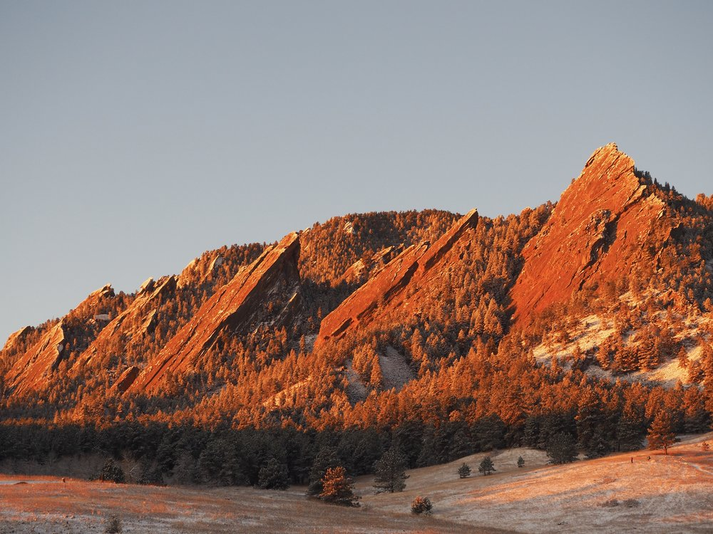 Sunrise on the snow dusting and Flat Iron mountains