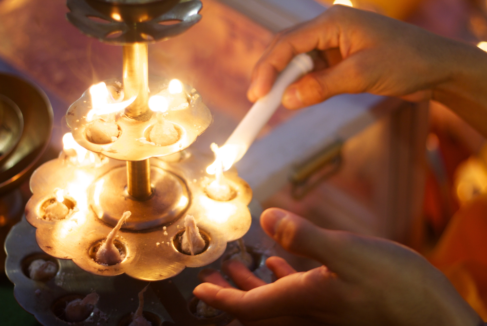 Hindu devotees light aarti lamps near Rishikesh, India.