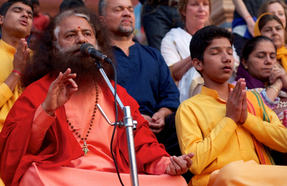 Pujya Swamiji sings at the sunset aarti on the banks of the Ganges River.