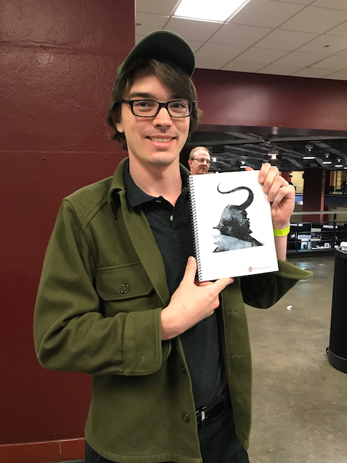 A student receives an IA sketchbook with an original Jeffrey Alan Love sketch on the inside cover.