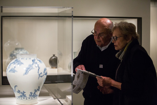 Museum visitors examine an 18th century Korean vase depicting a tiger smoking a long pipe, described by Miriam Mills, museum storyteller. May 2014.